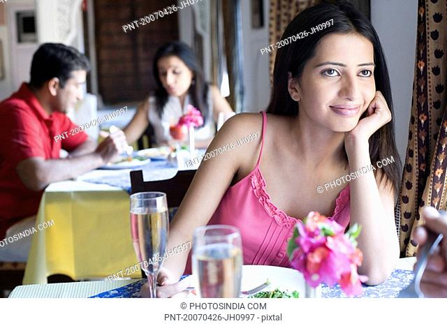 Young woman sitting in a restaurant with a mid adult couple having food in the background