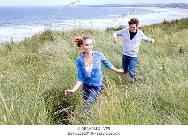 Young couple running through long grass with the background of the beach. They are both smiling and wearing casual clothing