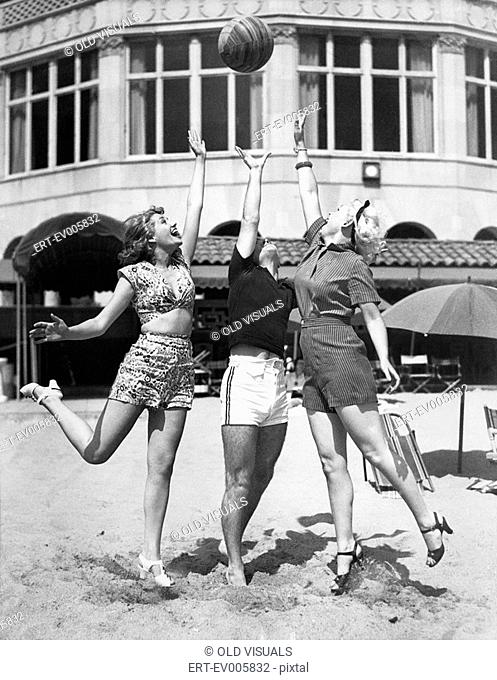 Three young women playing with a ball on the beach All persons depicted are not longer living and no estate exists Supplier warranties that there will be no...