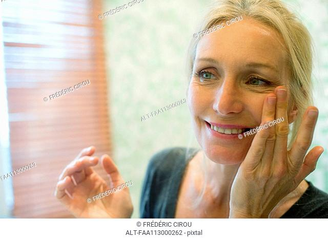 Mature woman looking at her reflection in mirror with hands on cheeks
