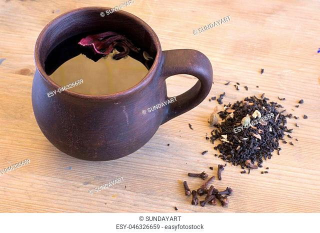 Abstract figure photography for editors, designers and artists with loam cup, wooden plank and spice tea with carnation