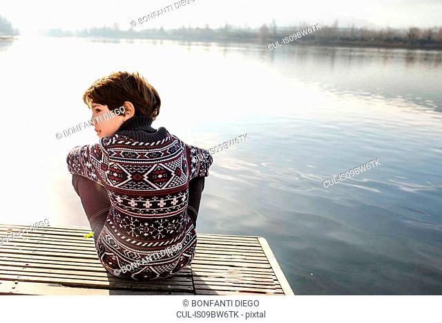Boy looking sideways from lakeside pier, rear view, Lake Como, Lecco, Lombardy, Italy