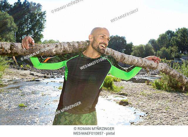 Smiling man doing CrossFit exercise with tree trunk on his shoulders