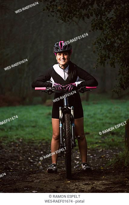 Portrait of smiling woman with mountain bike