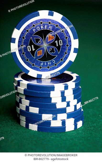 Stacked blue poker chips on green felt