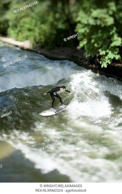 Teenager surfing in Eisbach, Munich, Bavaria, Germany