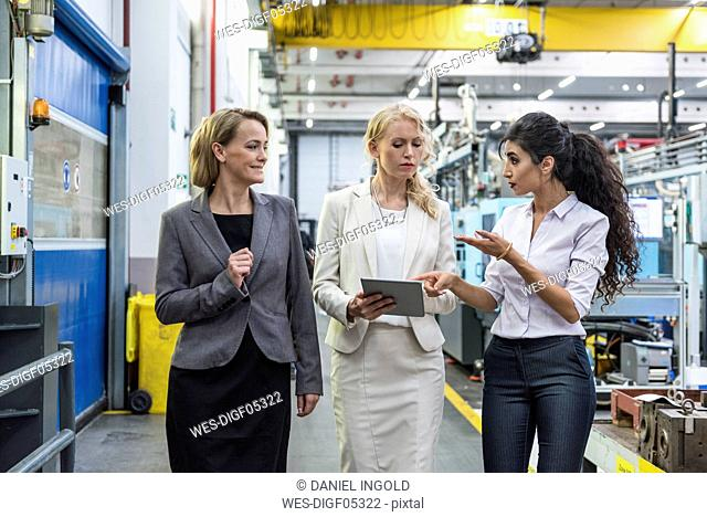 Three women with tablet talking in factory shop floor