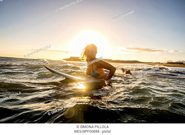 Spain, Tenerife, young female surfer at sunset