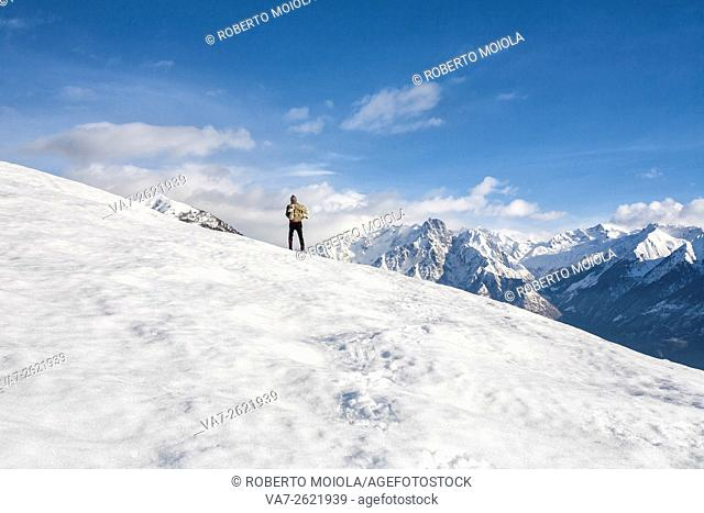 Hiker admires the snowy peaks of Masino Group Vercana Mountains High Lario Lombardy Italy Europe