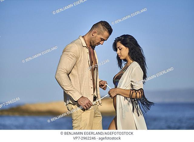 sensual boyfriend binding dress of girlfriend at Mediterranean beach. Greek ethnicity. In holiday destination Hersonissos, Crete, Greece