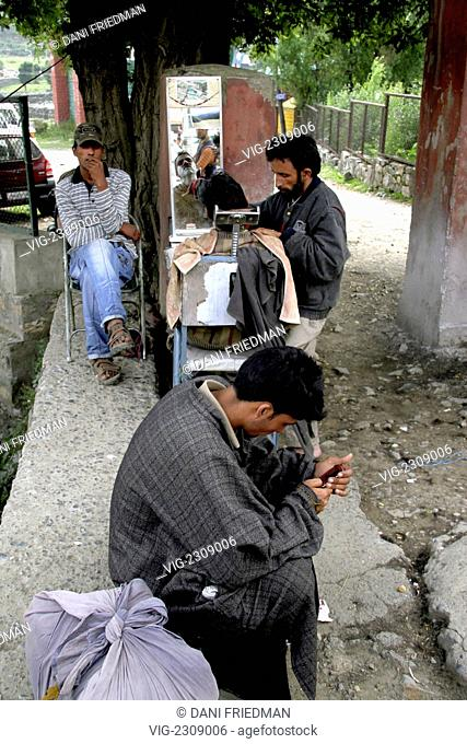 INDIA, PAHALGAM, 28.06.2010, A Kashmiri roadside barber gives a customer a shave under a tree as two men wait their turns