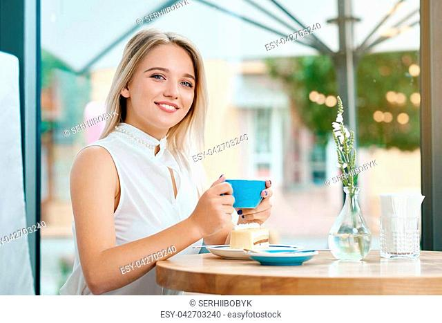 Cute blonde girl keeping cup of coffee outdoors, smiling. Wearing white blouse, looking at camera, sitting on wooden table in stylish cafe with modern interior