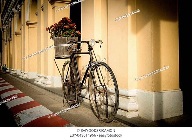Old bike parked at the road vintage style with flower in wood basket