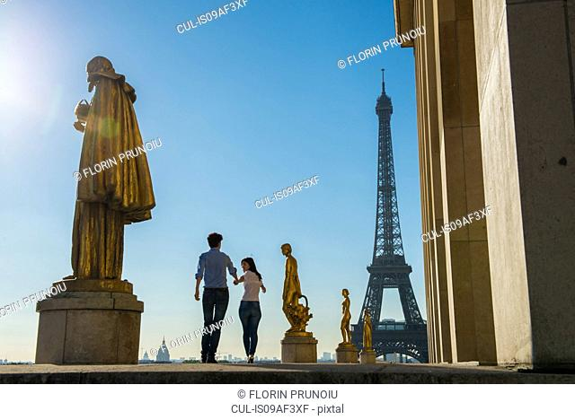 Young couple strolling near Eiffel Tower, Paris, France