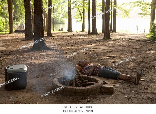 Man lying down next to campfire in forest, Arkansas, USA