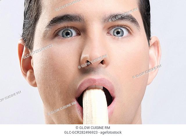 Portrait of a man eating a banana