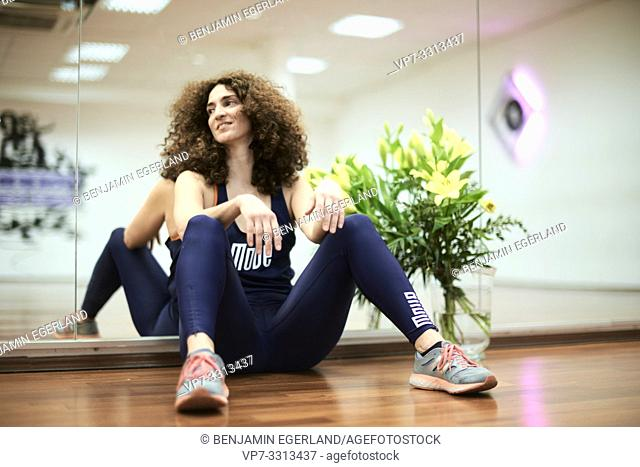 sporty mature woman sitting on floor in dancing fitness hall