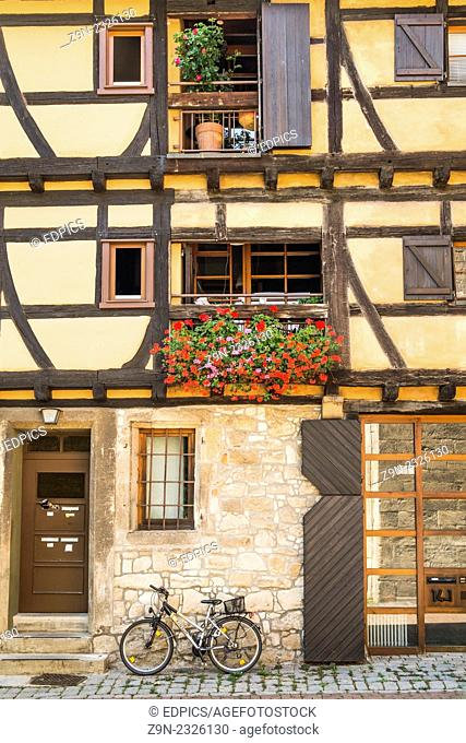 bicycle in front of the flower decked facade of a restored half timbered building in the historic part of tuebingen, baden-wuerttemberg, germany