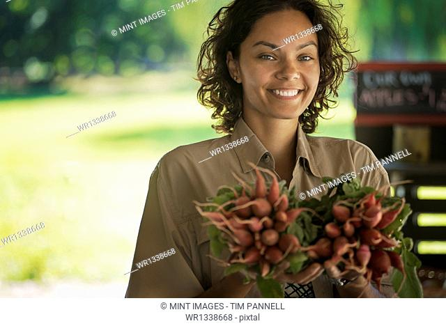 A woman carrying bunches of fresh red radishes with green leaves