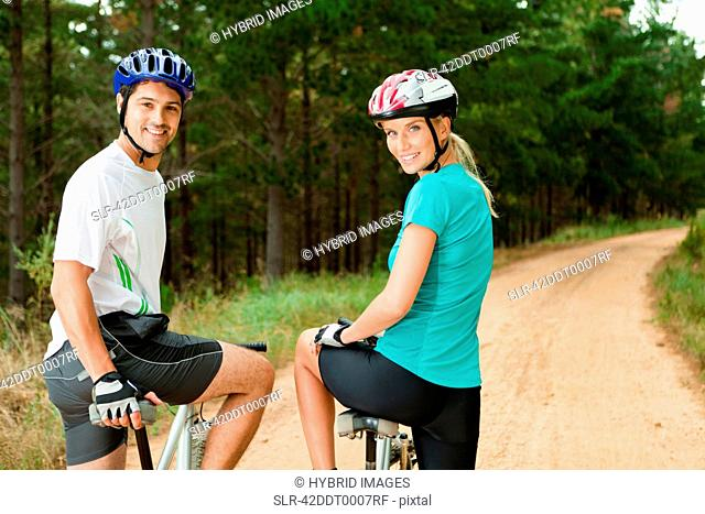 Couple mountain biking on dirt path