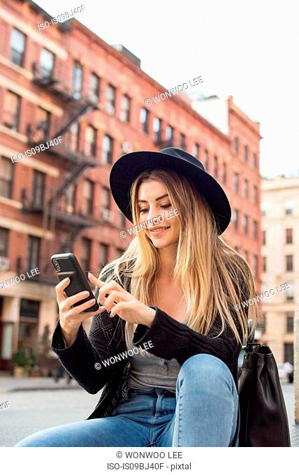 Woman looking at mobile phone smiling, texting, New York, USA
