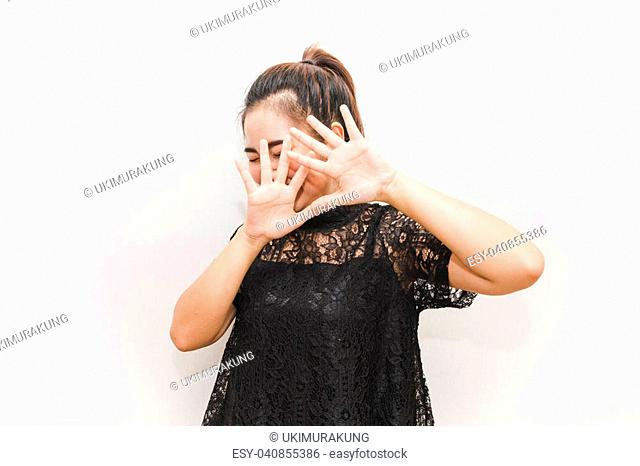 Asia woman put her hands up on her face look like defense afraid of something