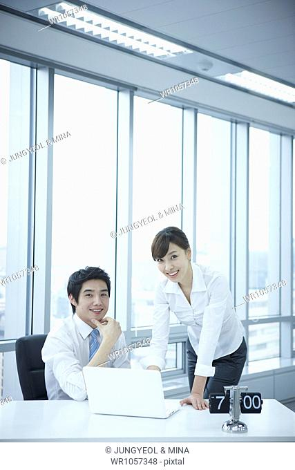 businessman and businesswoman in office smiling at camera