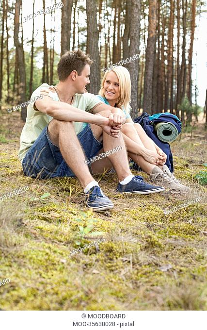 Full length of happy young hiking relaxing in forest