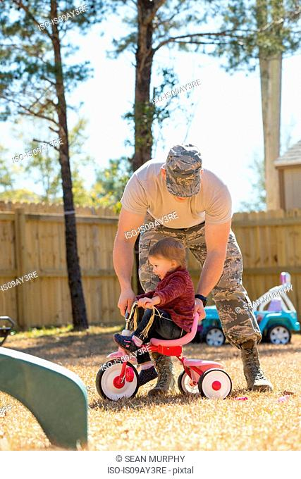 Young male soldier playing with toddler daughter on tricycle in garden at air force military base