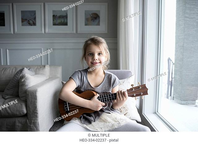 Portrait smiling girl playing ukulele at living room window