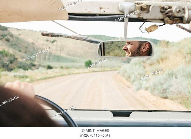 View through the windscreen of an open top jeep. Reflection of the driver in the rear view mirror