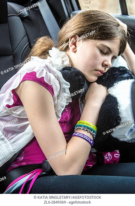 one caucasian preteen in the car sleeping and resting with stuff animals as her pillow