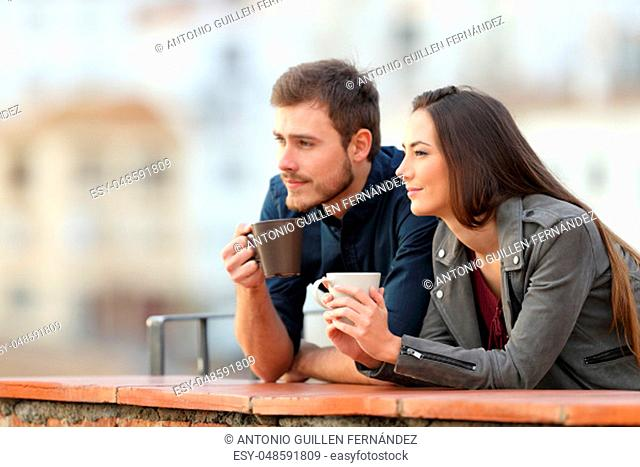 Happy couple relaxing drinking coffee in a balcony looking away on vacation