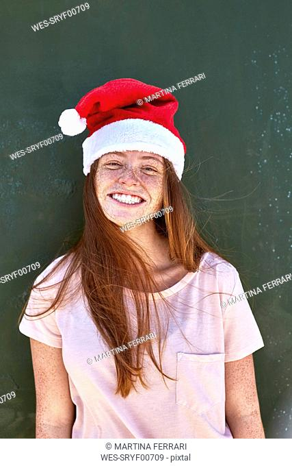 Portrait of smiling young woman wearing Christmas hat
