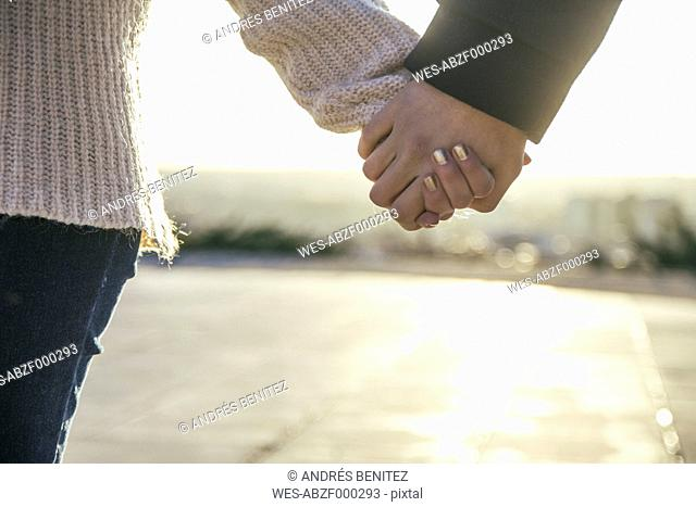Young couple holding hands at backlight, close-up