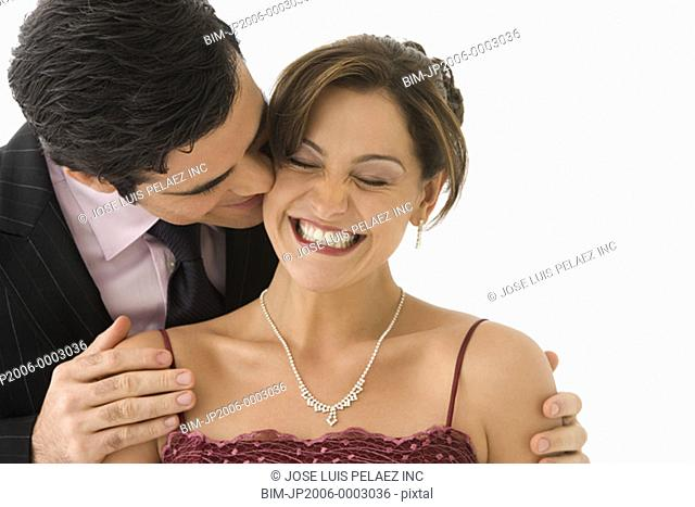 Studio shot of man kissing smiling woman on her cheek