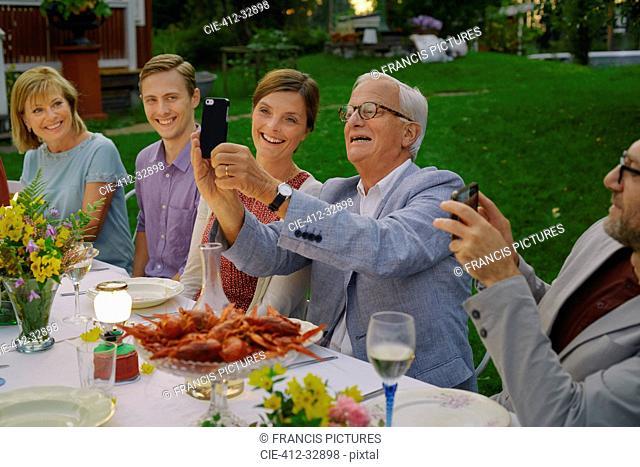 Senior man taking selfie with family at summer garden party dinner