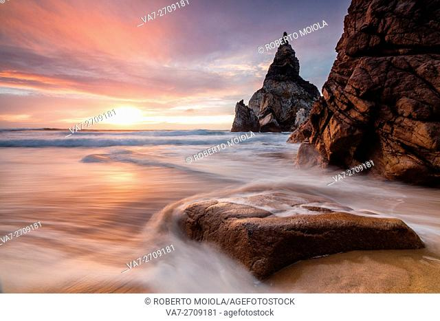 The fiery sky at sunset is reflected on the ocean waves and cliffs Praia da Ursa Cabo da Roca Colares Sintra Portugal Europe