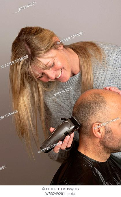Woman using portable electric hair clippers to give a balding man a crew cut
