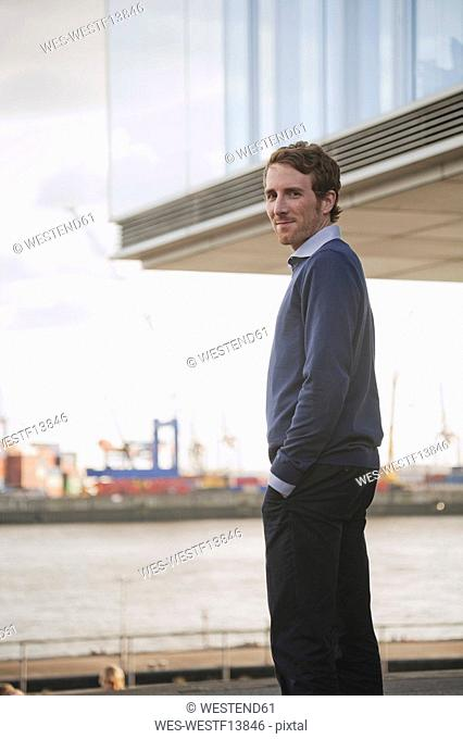 Germany, Hamburg, Businessman standing near quai, portrait