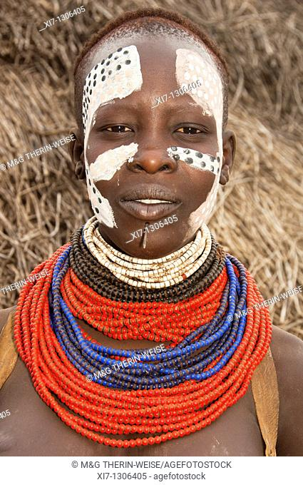 Young Karo woman with lots of colorful necklaces, lip piercing and facial paintings, Omo river valley, Southern Ethiopia