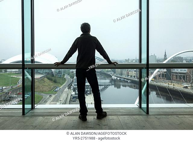 Gateshead, north east England, United Kingdom. A man looks out over the river Tyne towards Newcastle city centre from the viewing platform in The Baltic Centre...