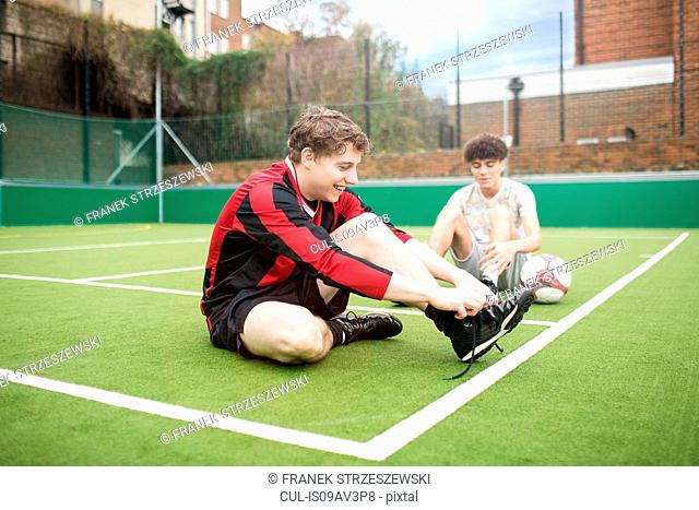 Two young men on urban football pitch, tying shoelaces