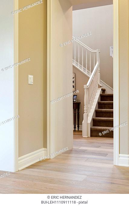 Hallway leading to stairs with banister at home