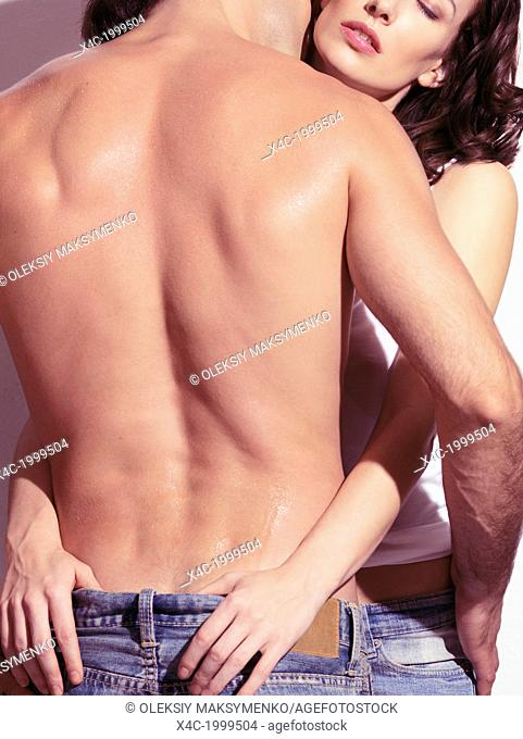 Young woman embracing a man with bare torso, closeup of back, rear view