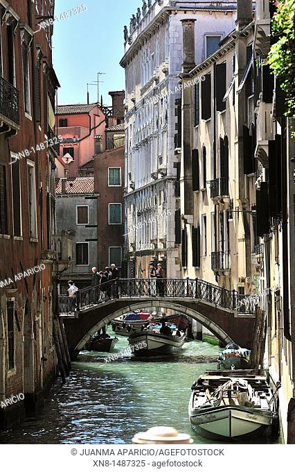 Vertical image of a channel with a small boat sailing under a bridge in Venice, Italy