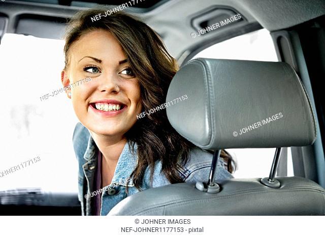 Smiling teenage girl in car looking behind
