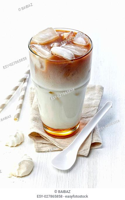 Iced coffee with caramel syrup in glass on wooden background