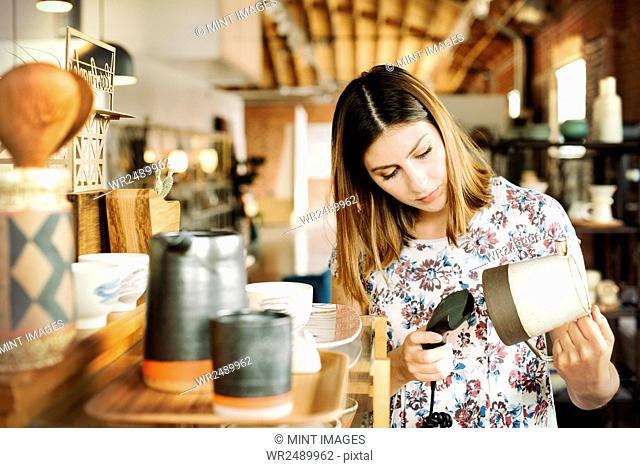 Young woman in a shop, scanning the barcode of a ceramic jug with a barcode scanner