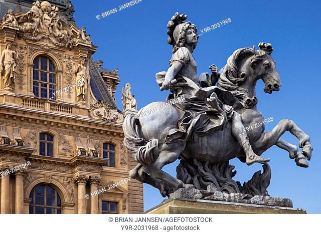 Equestrian statue of Louis XIV below the architecture of Musee du Louvre, Paris France
